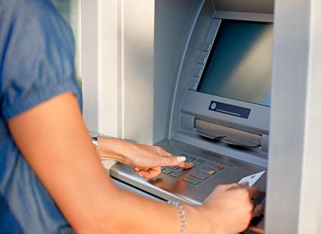 Kobieta za pomocą bankomatu trzymając kartę i naciskając numer bezpieczeństwa PIN na klawiaturze bankomatu