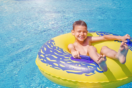 Cheerful smiling boy enjoys floating on inflatable ring in the swimming pool in aqua park