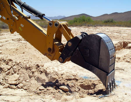 precisely: A construction Back Hoe digging the footing for a foundation that has been precisely marked.