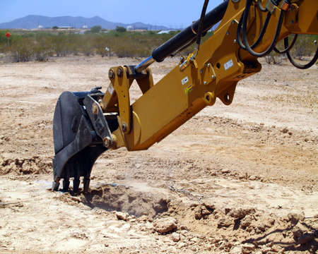 precisely: A construction Back Hoe precisely digging on a marked spot on the ground. Stock Photo
