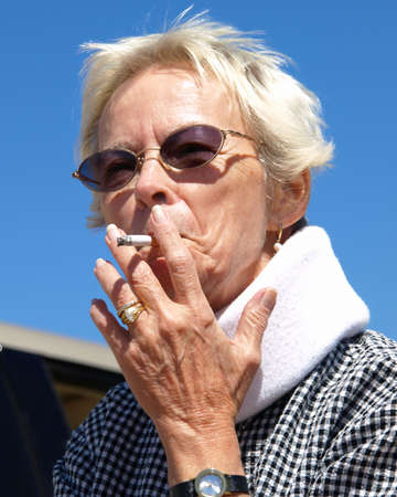 puffing: An elderly woman puffing on her cigarette.