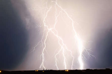discharge time: A massive discharge of lightning illuminating a column of rain during a night time monsoon storm in Arizona. Stock Photo