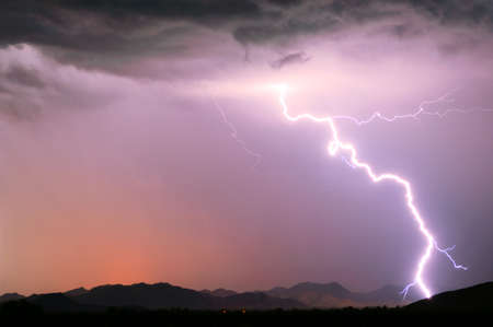 A bright lightning strike illuminating the Buckeye Foothills in Arlington Arizona during the 2012 Monsoon season. photo