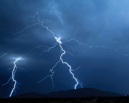monsoon: A pair of lightning bolts twisting through the air on their way down to a mountain near Arlington Arizona during the 2012 Monsoon season.
