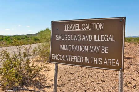 prevalent: A caution sign put up on a remote road in Arizona indicating the prevalent illegal activity in the area. Stock Photo