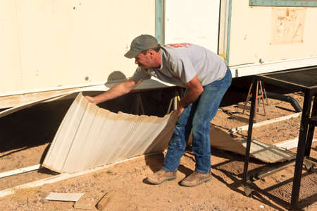skirting: A construction Handyman removing the last pieces of skirting from a mobile home that is being renovated.