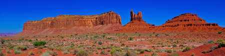monument valley view: A panorama view of Monument Valleys three famous formations known as Eagle Mesa, the Sitting Hen, and Douglas Butte. This is composed of 5 sequential photos stitched together. Monument Valley straddles the border of Arizona and Utah on the Navajo Indian  Stock Photo