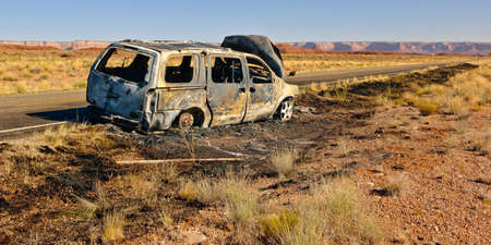 burned out: The burned out shell of a vehicle along US Highway 163 just north of Mexican Hat in Utah. This road leads to the Valley of the Gods. Nobody was hurt during this fire, but if the people were on their way to visit the Valley of the Gods they were out of luc Stock Photo