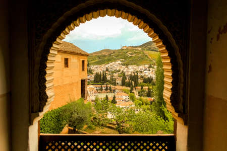 View from a window facing the downtown of Granada city. Arch windows of arabic origins and city architecture of arabic influence. Moors.