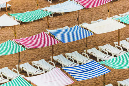Colorful umbrellas, canopies, tents and chairs, Lagos Portugal. Very colorful beach tents, sunblinds, awnings.