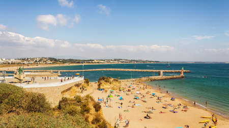 Beautiful Summer day at Praia da Batata, Lagos, Portugal. Lots of people, tourists and locals bathing in the sun, and swimming in the blue and green pure ocean water.