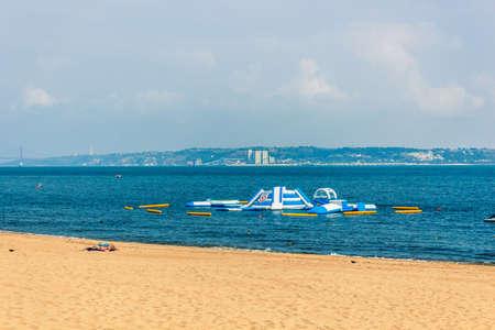 Sea water slide at the beach, Oeiras Portugal. Regular beach summer vacation beach near Lisbon, with built in recreational water slides in shallow water.