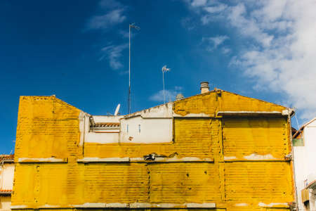Yellow insulating material on building in Granada, Spain. Blue sky, high contrast with yellow building. Stock Photo