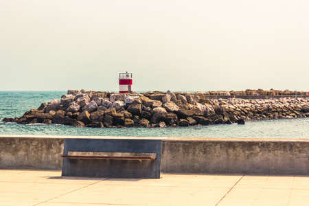 Small Lighthouse with red and white stripes in Marina de Oeiras. View with a beautiful metallic street bench and some harbour rocks called breakwaters.