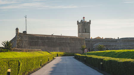 Saint Julian Fortress (Forte de Sao Juliao da Barra) entrance with green garden, tower, and lighthouse, road with tony lampposts, Oeiras, Lisbon