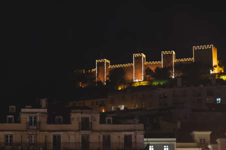 Saint George Moorish castle occupying a hilltop overlooking the center of Lisbon and Tagus River. Night illuminations during Christmas holiday season