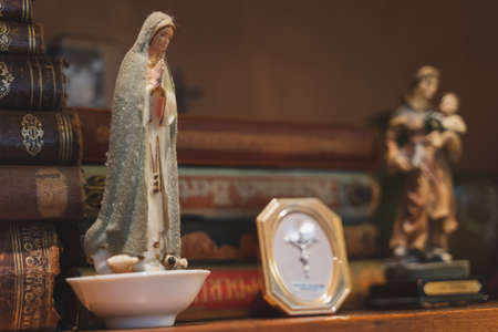 Statue of Mary, mother of Jesus, according to the New Testament and the Quran sitting on an old shelf filled with very old books.
