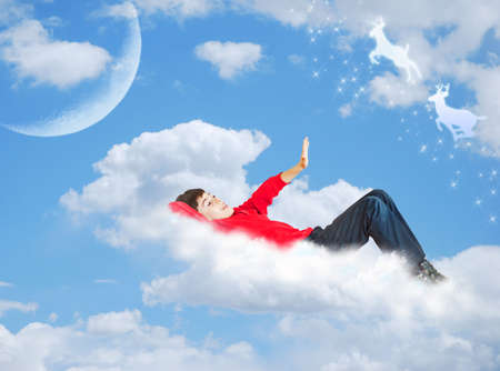 the boy is resting on the cloud Stock Photo