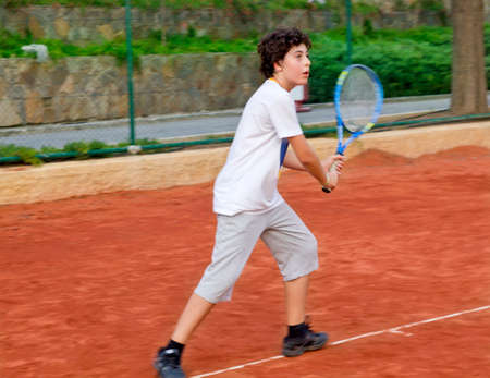 The boy is playing tennis Stock Photo