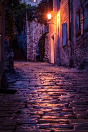 Oude geplaveide straat in de nacht-Pula, Kroatië