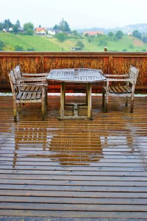 Terraza de madera mojada con mesa y sillas despu�s de la lluvia