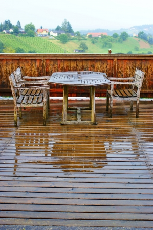 Wet wooden terrace with table and chairs after rain  photo