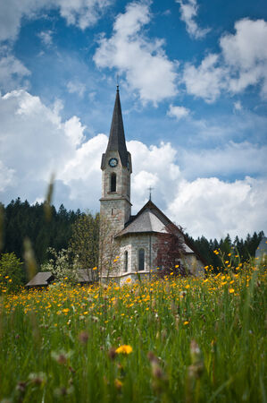 orte: Church in the mountains with flowering meadow  ,Gosau,Salzkammergut,Austria   Stock Photo