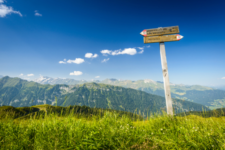 Tourist paths directions and travel time shown on a traditional direction signs at the Dolomites mountains, Italy  photo