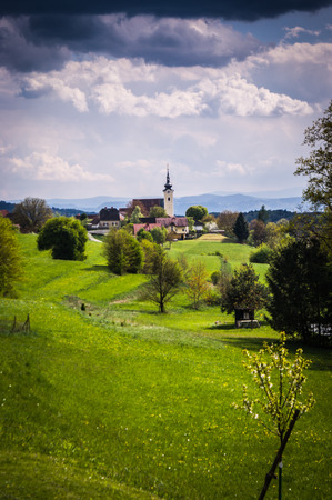 Spring landscape with fields, meadows and village in background photo