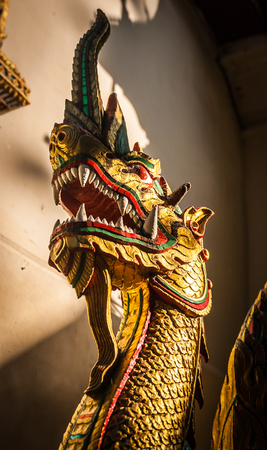 Thailands golden dragon head by old temple  photo