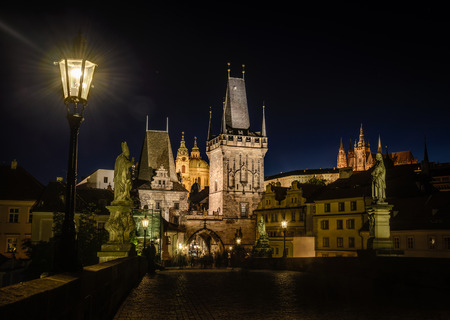 Night view of lantern on a Charles Bridge and Prague Castle in background,Czech Republic  photo
