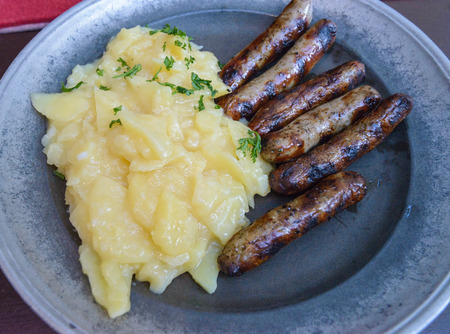 pewter: German traditional food:fried sausages with potatoes salad served on a pewter plate.