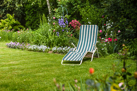 reposera: Relaxing place- deck chair in flowering ,summer garden.