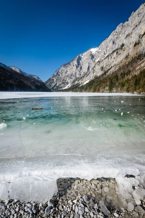 turquise: Winter landscape with interesting pattern on frozen lake and mountains in background. Stock Photo