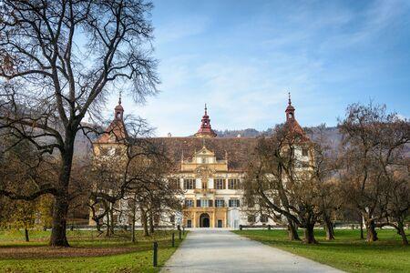 steiermark: Autumn park and front facade of the Eggenberg castle in Graz, Styria, Austria