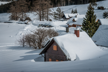 christmas village: Winter landscape with mountain village covered with snow. Stock Photo