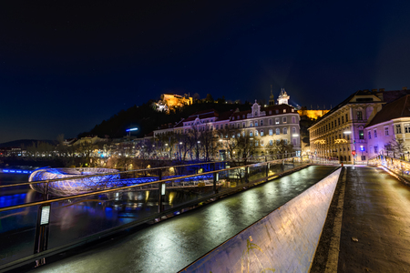 GRAZ, AUSTRIA - DECEMBER 24, 2015: Wall with Murinsel river, castle and clock tower Uhrturm he Schossberg in Graz, Austria.Old town of Graz is the UNESCO World Heritage.