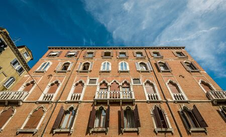 faade: A view of old buildings against blue sky in Venice, Italy