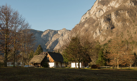 Autumn landscape of Bohinj, Slovenia with antic authentic house with mountains in background.