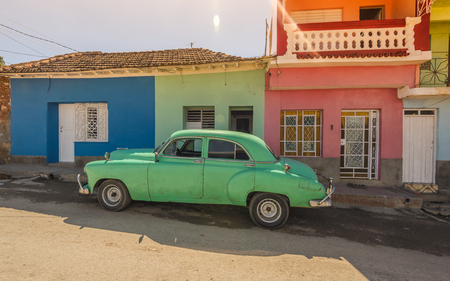 Green car on the front of the green house in the UNESCO World Heritage city center of Trinidad Cuba. Stock Photo