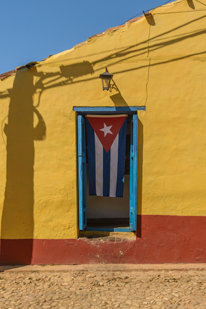 Cuban flag on yellow house in the UNESCO World Heritage city of Trinidad Cuba. Stock Photo