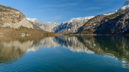 Panoramic scenic view in Austrian alps. Hallstatt mountain village at Hallstatt lake. Sunny day lake view from Hallstatt alps mountains. Location: resort village Hallstatt, Austria, Alps. Europe.
