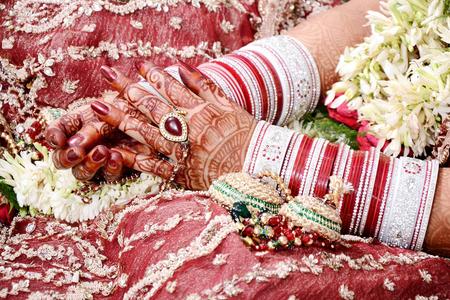 Nahaufnahme der dekorativen Hände der indischen Braut mit goldenem Schmuck. Selektiver Fokus wird verwendet.