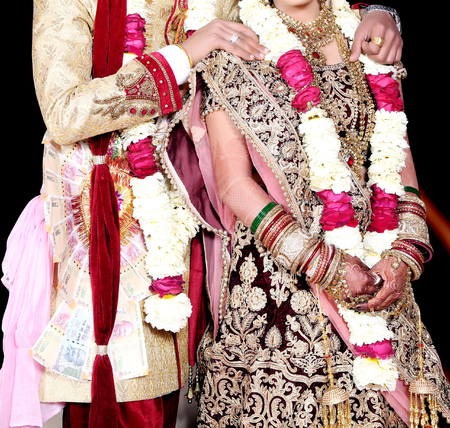 Indian bride and groom pose for beautiful portraits after their colorful jaimala ceremony ( garlands ceremony ) Stock Photo - 104230331