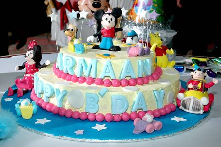 Colorful birthday cake decorated with little cartoon characters on the top.