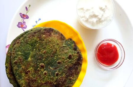 Spinach Paratha flatbread Indian cuisine served with traditional Punjabi Dahi and Chutney