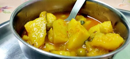 Indian Aloo Mutter curry - Potato and Peas immersed in an Onion Tomato Gravy and garnished with coriander leave