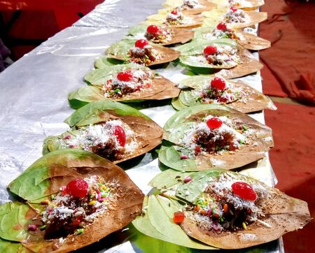 Betel leaf or meetha banarasi paan garnished with cherry fruit and all kind of indian banarasi ingredients or masala for sale.