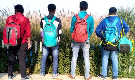 backside of four young boys with hanging bags in the park