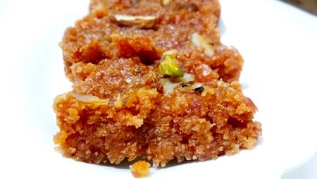 Homemade carrot halwa, traditional indian sweet, on white plate